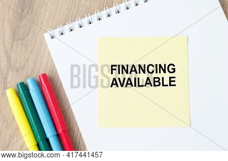 Text Financing Available On Yellow Paper On A Notepad That Sits On A Wooden Table With Colored Flama