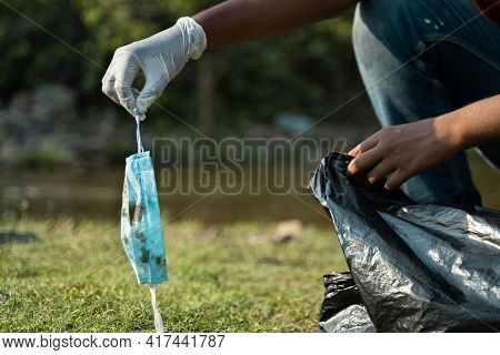 Focus On Hand With Gloves, Close Up Of Frontline Worker Hands Collecting Face Mask And Placing Insid