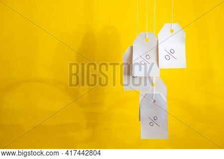 White Tags With The Percent Sign Hang On Strings On A Yellow Background With Shadows. Commerce, Disc