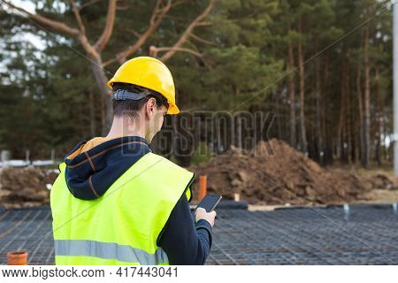Construction Worker Talks On A Smartphone In A Yellow Helmet And Protective Vest Against The Backgro