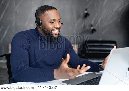 Focused Young Businessman In Eyewear Wearing Headphones, Holding Video Call With Clients On Laptop.