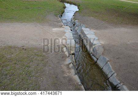 A Stream Flows Through A Park Path In A Romantic Park. The Bridge Here Is Not Just A Slit Laid Out A