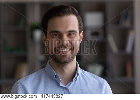 Headshot Portrait Of Smiling Young Caucasian Man Indoors