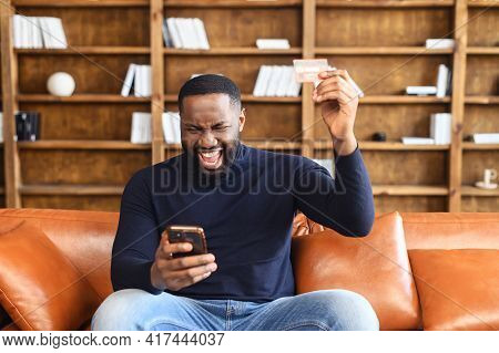 Happy Hilarious Young Multiracial Man Involved In Online Shopping, Celebrating Getting Gift Or Winni