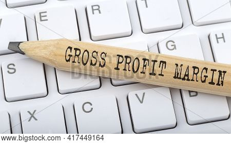 Text Gross Profit Margin On Wooden Pencil On White Keyboard. Business