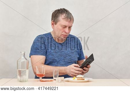 A Drunken Business Man With A Smartphone Sits Alone At A Table With Alcohol.