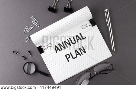 Text Annual Plan On Notebook And Office Tools On The Gray Desktop