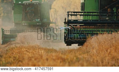 Warsaw, Poland 10.08.2020 - Two Combine Harvester In A Golden Wheat Field. The Dust Cloud Can Be See