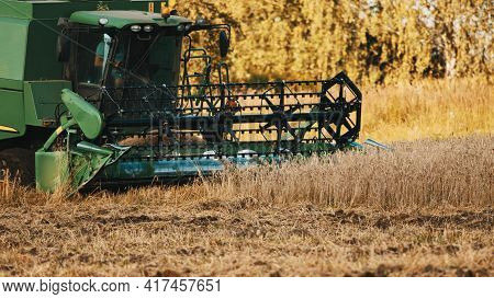Warsaw, Poland 10.08.2020 - Sideview Of A Combine Harvester In A Golden Wheat Field. Worker Driving