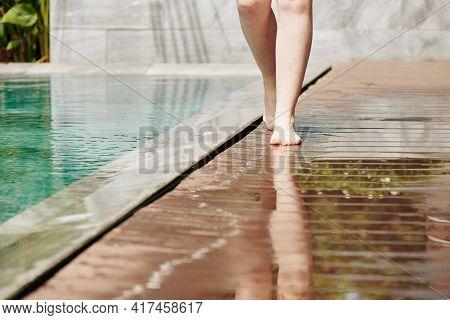 Legs Of Woman Walking Along Edge Of Swimming Pool Of Spa Hotel