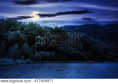 Lake Among Mountain Landscape In Spring At Night. Beautiful Countryside Scenery With Forest On The S
