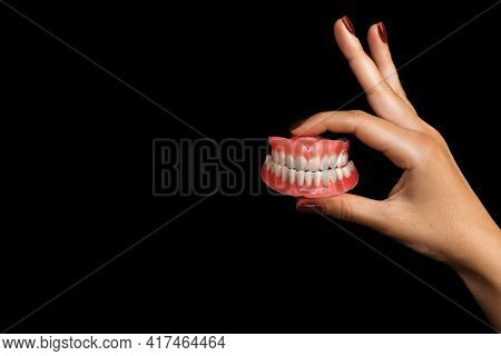 The Dentist Is Holding Dentures In His Hands. Dental Prosthesis In The Hands Of The Doctor Close-up.