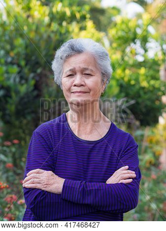 Elderly Woman With Short White Hair Standing Smiling And Arm Crossed In The Garden. Asian Senior Wom