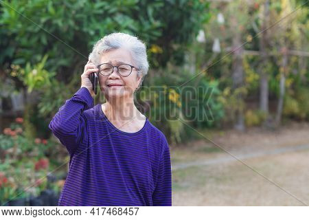 Portrait Of Elderly Woman Talking On Her Mobile Phone With Delight As His Listens To The Conversatio