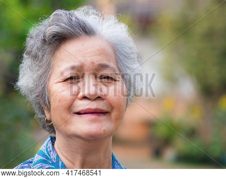 Portrait Of Elderly Woman With Short White Hair And Standing Smile In Garden. Asian Senior Woman Hea