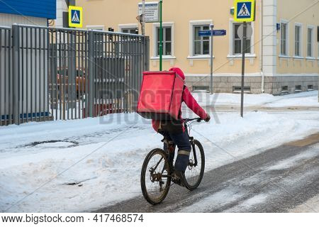 Moscow, Russia - January 17, 2021: Food Delivery Man On Bicycle Working At Winter On Dirty City Stre
