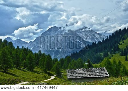 Alpine Hut On Pasture In Front Of Wood And Mountains With Clouds