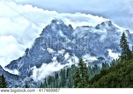 Wild Clouds Forming On Mountain Ridge Ready For Mountaineering Hiking With Valley With Wood Forest
