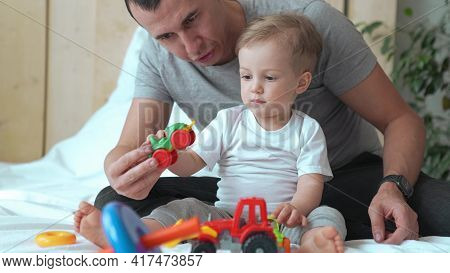 Happy Family At A Home. Dad And Son Play Toy Car And Tractor. Happy Family At Home Together Concept.