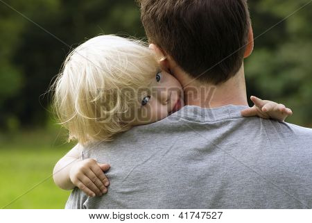 Closeup Portrait Of Young Toddler Baby Boy Resting On Daddy's Shoulder