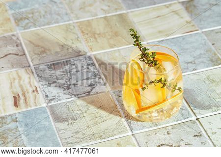 Refreshing Cocktail With Ice, Orange And Thyme. Refreshing Summer Homemade Alcoholic Or Non-alcoholi