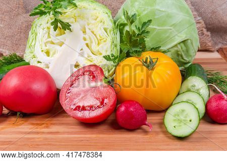 Different Fresh Washed And Partly Cut Vegetables And Greens On Wooden Cutting Board, Fragment Close-