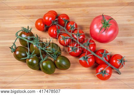 Two Clusters Of Fresh Ripe Red Cherry Tomatoes And Cherry Tomatoes Kumato, Single Ordinary Pink Toma
