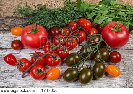 Multicolored Fresh Ripe Cherry Tomatoes And Ordinary Pink Tomatoes, Greens On A Old Cracked Wooden S