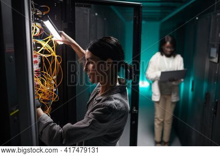 Side View Portrait Of Female Network Engineer Connecting Cables In Server Cabinet While Working With