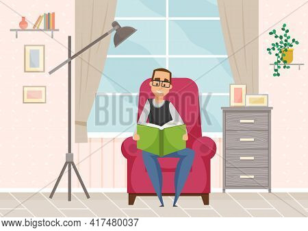 Adult Man In Glasses Reading Book Sitting In Armchair In Cozy Livingroom Interior, Resting At Home