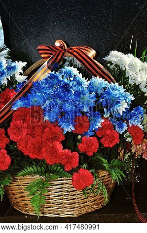 9 May holiday. 9 may background. 9 May outdoors.Flowers with George ribbon during the celebration of May 9 at the memorial stele City of Military Glory in Veliky Novgorod, Russia