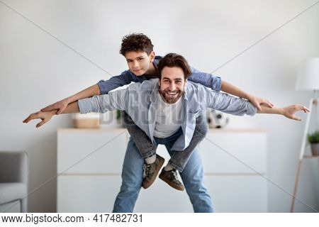 Playful Father And Son Having Fun Together, Daddy Riding Boy On Back Like Flying On Plane At Home In
