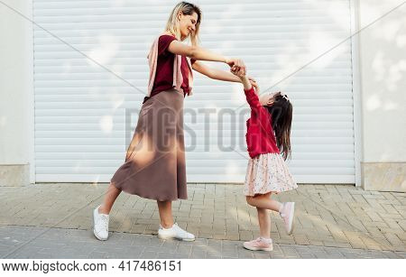 Horizontal Image Of A Happy Mother Looks To Her Little Girl Holds The Hands Together And Dancing Out