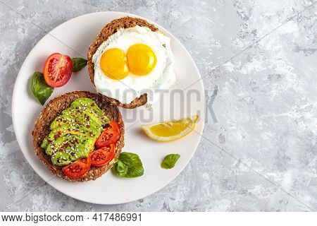 Avocado Toast Breakfast With Fried Egg, Top View. Fresh Avocado Burger, Vegetarian Snack, Delicious