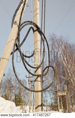 Electricity Concept, Concrete Pole With High Voltage Cable Coiled Into A Coil. Close-up Against The