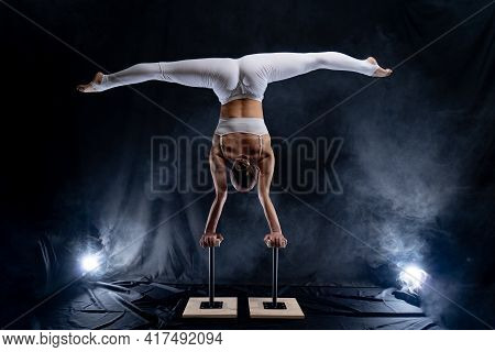 Flexible Circus Artist - Female Acrobat Doing Handstand On The Back And Smoker Background