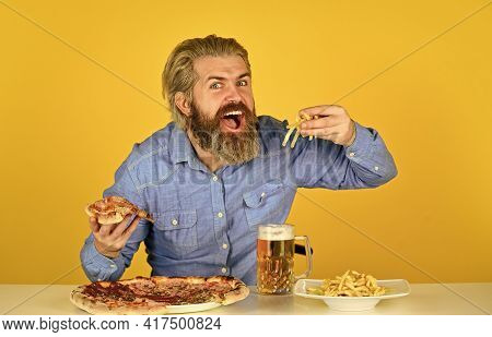 Cheerful Man Bearded Hipster Eat Pizza. Dinner At Pub. Hungry Man Going To Eat Pizza And Drink Beer.