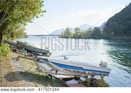 Docked Boats On The Lake Como District In Italy On Sunny Day. Alp Mountains On Background