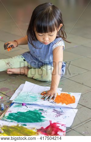 Selective Focus At Dirty Hand Of Asian Child Baby Girl Drawing And Painting Colours On The Paper In