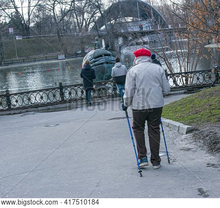 Dnepropetrovsk, Ukraine - 03.21.2021: Tired Woman Of Mature Age Walks Around The City. A Woman Holds