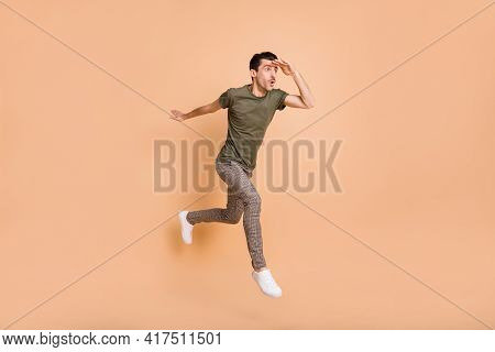 Full Length Body Size Photo Of Jumping High Man Looking Forward Far Hand Near Forehead Isolated On P