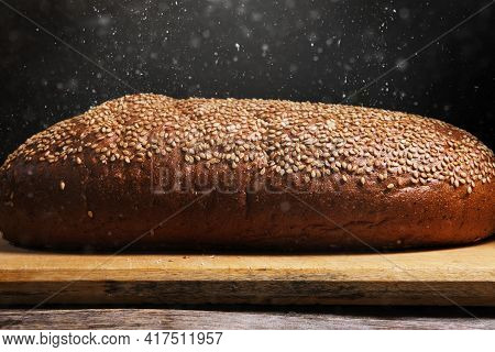 Loaf On Cutting Board, Crust Is Sprinkled With Sesame Seeds And Sprinkled With Flour.
