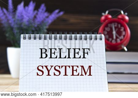 Belief System - Words In A Notebook Against The Background Of Books, Alarm Clock And Lavender. Busin