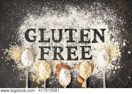 Gluten free written in flour on vintage baking sheet and spoons of various gluten free flourfree baking concept