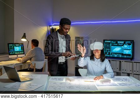 African American employee synchronizing tablet virtual reality headset of Asian colleague while they designing car in 3D