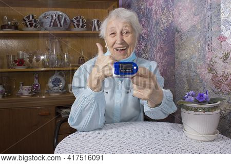 Senior Woman Using Pulse Oximeter At Home To Test Oxygen Level In Blood