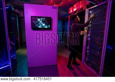 Serious young Black man standing with tablet at server cabinet and checking blade server while managing servers