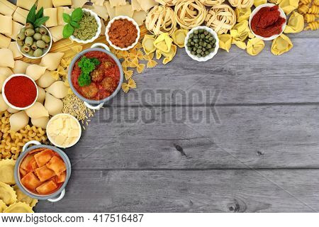 Italian healthy food border with pasta collection and ingredients high in antioxidants, anthocyanins, fibre, lycopene and  protein. Top view on rustic silver wood background.