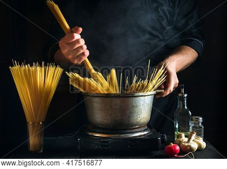 Cook Cooks Italian Pasta In A Restaurant Kitchen. Close-up Of A Chef Hand Holding Spaghetti. Vegetab