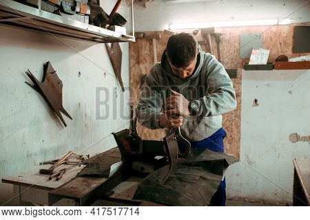 Tinsmith Blacksmith Use Hammer Working In His Workshop. Blacksmiths Workshop. Young Tinsmith In His